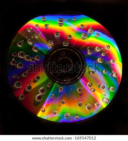 Closeup of water drops on a multicolored surface of CD  - stock photo