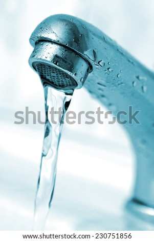 Closeup of water running from tap. Macro, shallow depth of field - stock photo