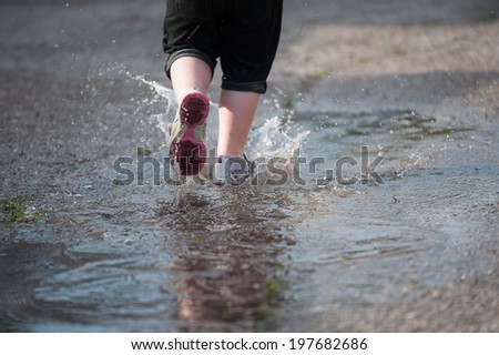 Closeup of water splashing up from a little girl's shoes as she runs through a puddle in the street, selective focus on the stream of water behind her shoe.