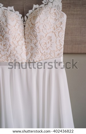 closeup of wedding dress hanging over the bed in hotel room during the bride preparation