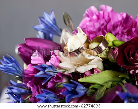 Closeup of wedding rings on a bouquet - stock photo