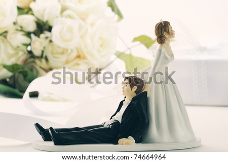 Closeup of whimsical wedding cake figurines on white - stock photo