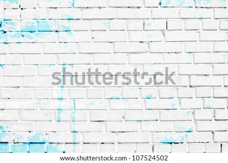 closeup of white brick wall with blue paint stains - stock photo