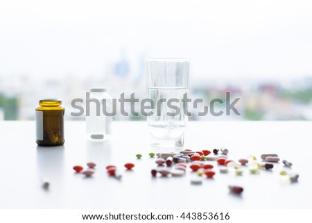 Closeup of white desktop with colorful pills, medicine bottles and glass of water on blurry city background - stock photo