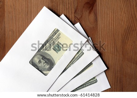 Closeup of white envelopes and dollar bills inside on wooden background - stock photo