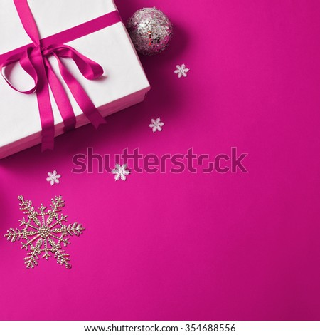 Closeup of white gift box with pink ribbon on pink background, small Christmas ornaments and decoration around it. Square format, mild retouch, matte look filter, copy space, vibrant color, high angle - stock photo