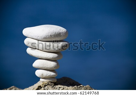 Closeup of white pebbles stack over blue sea - stock photo