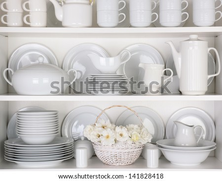 Closeup of white plates and dinnerware in a cupboard. A basket of white roses is centered on the bottom shelf. Items include, plates, coffee cups, saucers, soup tureen, tea pot, and gravy boats.