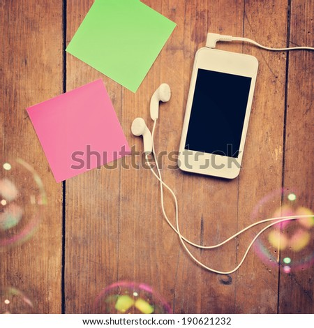 Closeup of white smartphone with black screen with headphones, sticky notes and bubbles on wooden surface. Square image format. Instant photo style retro filter. - stock photo