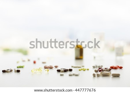Closeup of white table with colorful pills and capsules, blurry medicine bottles and a glass of water. Selective focus - stock photo