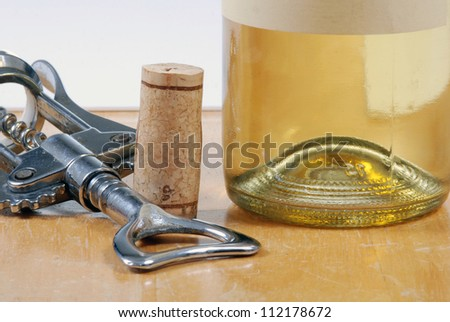 Closeup of wine bottle near cork and corkscrew - stock photo