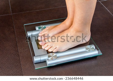 Closeup of woman feet standing on bathroom scale. Health and weight concept. - stock photo