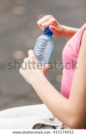 Closeup of woman female hands with bottle of water.