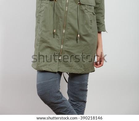 Closeup of woman girl in dark green khaki coat and posing in studio. Winter autumn fall fashion. - stock photo