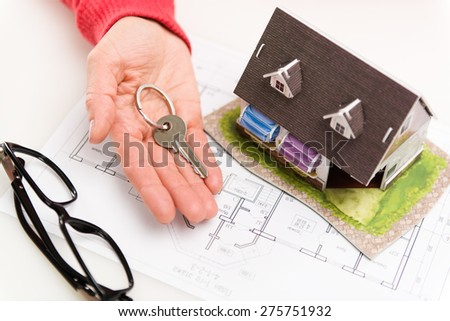Closeup of woman hand giving residential house key to client. Concept of housing rent and sale. Shallow depth of field. - stock photo