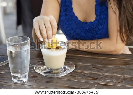 Closeup of woman hand with cookie and cup of latte coffee in the coffee shop outdoors.  - stock photo