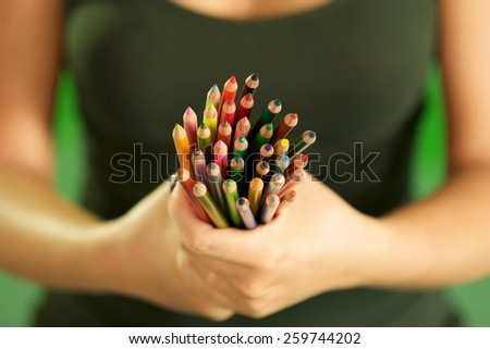Closeup of woman hands showing bunch of colorful pencils at camera. Narrow focus - stock photo