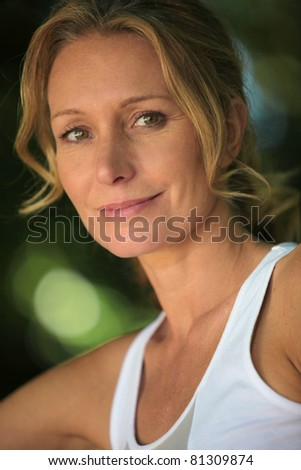 Closeup of woman in white vest in leafy environment - stock photo