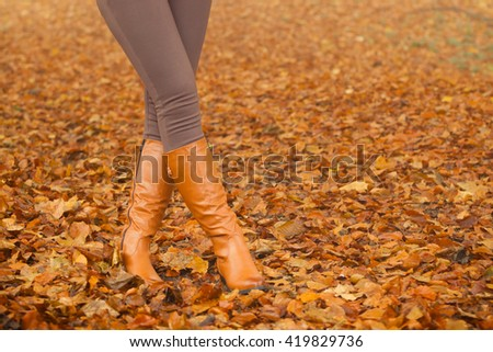 Closeup of woman legs in brown boots. Girl in autumn park forest. Fall winter fashion. - stock photo