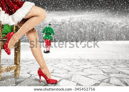 closeup of woman legs with red heels on stone floor with green elf and snow space