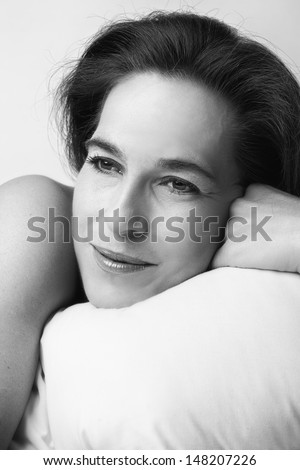 Closeup of woman on bed boudoir black and white artistic conversion - stock photo