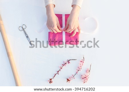 Closeup of woman packs gifts, step by step - stock photo