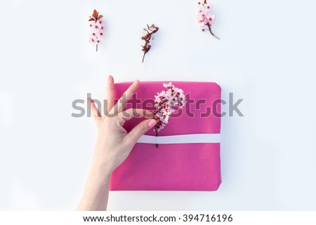 Closeup of woman packs gifts with pink paper and flowers - stock photo
