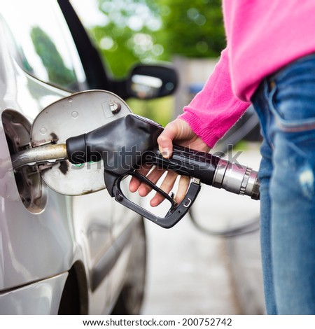 Closeup of woman pumping gasoline fuel in car at gas station. Petrol or gasoline being pumped into a motor vehicle car. - stock photo