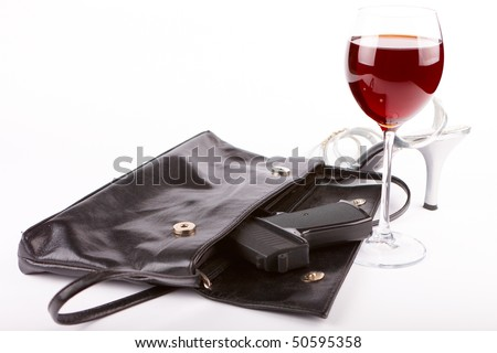 Closeup of woman's bag wit pistol, glass of red wine and isolated and high heel boot over white background - stock photo