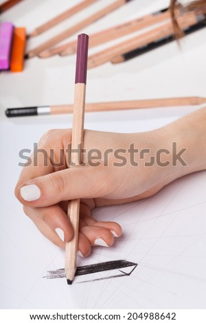 Closeup of woman's hand drawing on paper - stock photo