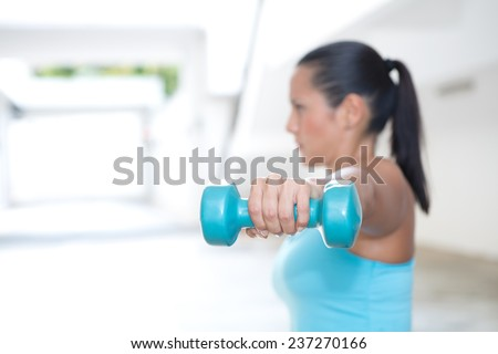Closeup of woman's hand holding blue dumbbell for her arm training, outdoor. - stock photo