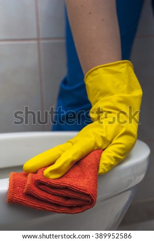 Closeup of woman's hand in yellow glove with rag cleaning the toilet. Housework and cleaning concept. - stock photo
