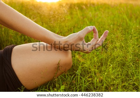 Closeup of woman's hand meditating in a open field.  - stock photo