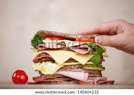 Closeup of woman's hand on burger in coffee shop - stock photo