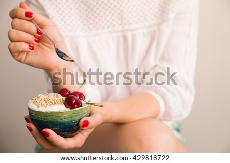 Closeup of woman's hands holding a cup with organic yogurt with oats and cherries.  Breakfast or snack. Healthy eating and lifestyle concept. - stock photo