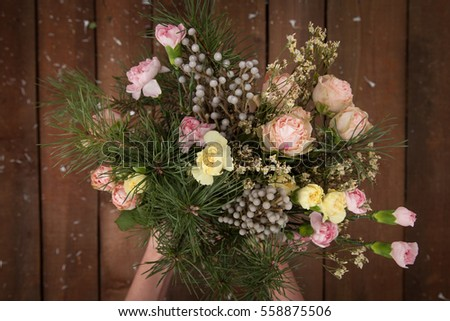 Closeup of woman's hands holding beautiful winter bouquet of flowers on the wooden background.