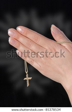 Closeup of woman's hands together holding a cross & chain - stock photo