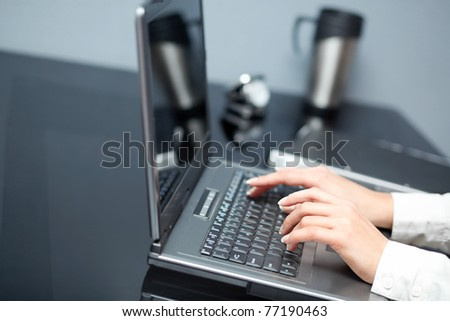 Closeup of woman's hands touching notebook (laptop) keys during work. In office interior. - stock photo