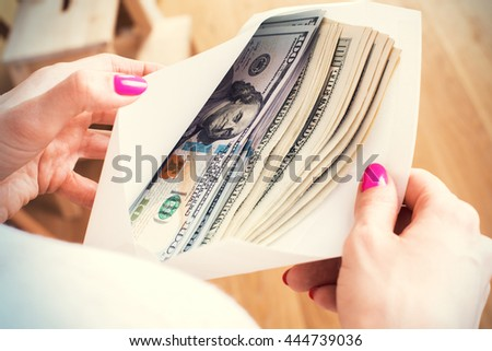 Closeup of woman's hands with envelope full of dollar banknotes on wooden background. Concept of corruption and bribery - stock photo