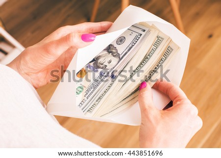 Closeup of woman's hands with envelope full of money on wooden background. Concept of corruption and bribery