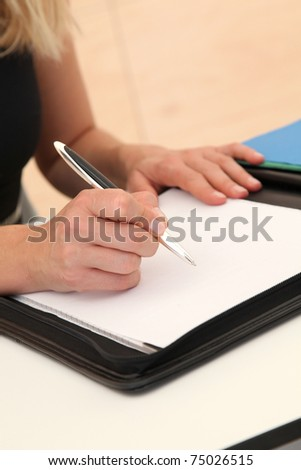 Closeup of woman signing contract