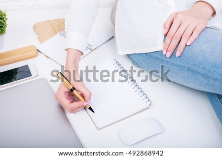 Closeup of woman sitting on white desktop with closed laptop, computer mouse, smartphone, supplies, plant, other items and writing in empty spiral notepad. Mock up