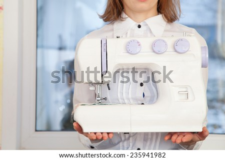 Closeup of woman tailor holding sewing machine - stock photo