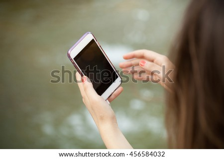 Closeup of woman taking a photo with her phone - stock photo