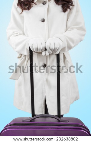 Closeup of woman wearing winter clothes and holding a luggage in studio with blue background - stock photo