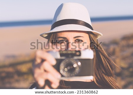 Closeup of woman with an old camera at the beach. Retro filter effect and shallow dof - stock photo