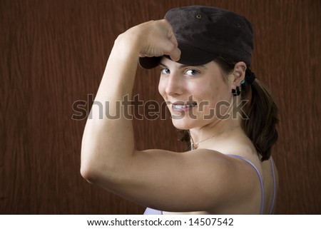 Closeup of woman with blue eyes wearing a cap flexing her bicep - stock photo