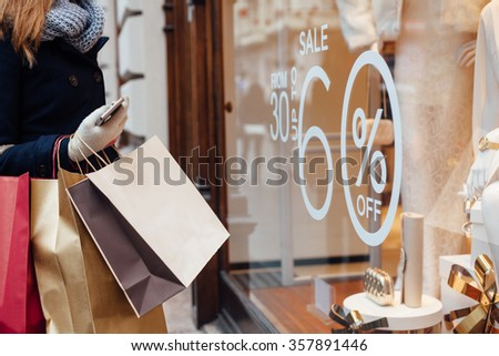 Closeup of woman with shopping bags in front on store window