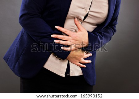 Closeup of woman with stomach issues against gray background