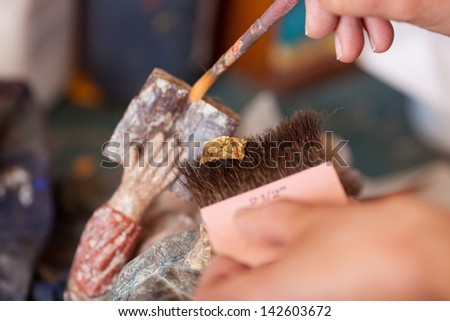 Closeup of woman working with golden paper on statue in workshop - stock photo